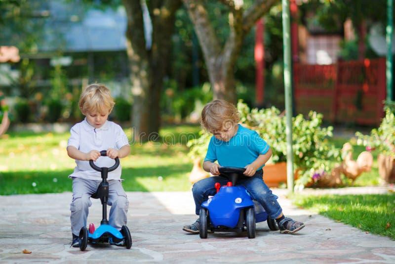 Två små barn för små bröder som spelar med bilar royaltyfri foto