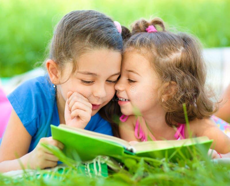 Två små flickor är läseboken fotografering för bildbyråer
