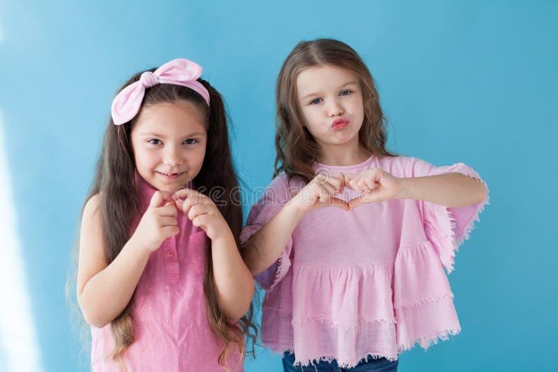 Två små flickor är systerflickvänner i en rosa klänning royaltyfria bilder