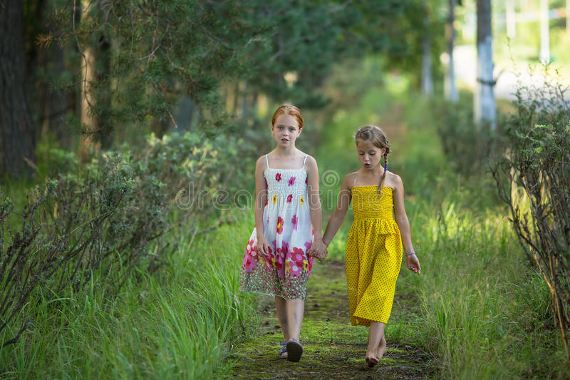 Två små flickor går till och med parkera fotografering för bildbyråer