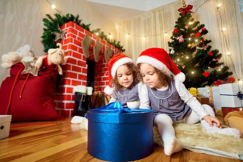 Två små flickor i lock av Santa Claus sammanträde på golvintelligensen royaltyfri foto