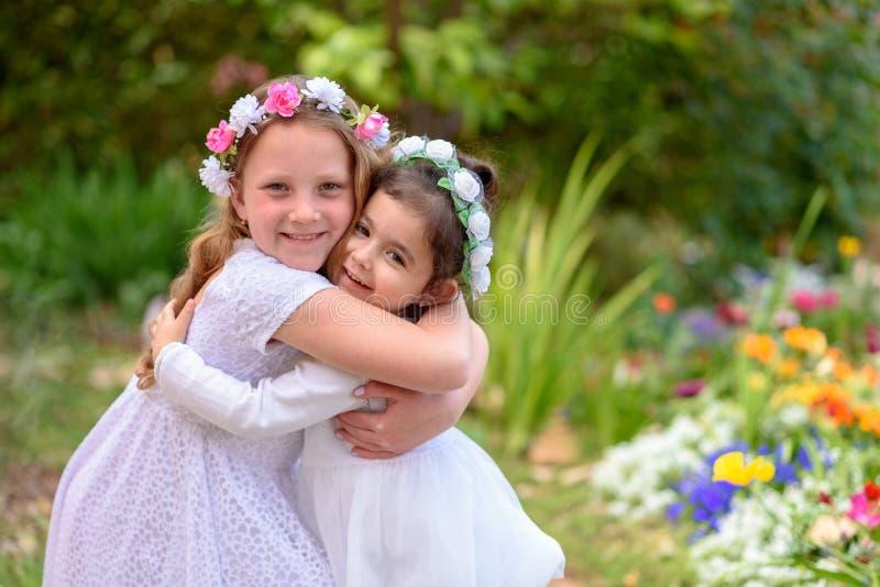 Två små flickor i vita klänningar som har gyckel en sommarträdgård royaltyfri bild