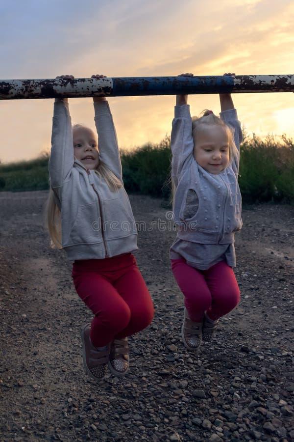 Två små flickor, kopplar samman och att ha gyckel i solnedgången royaltyfri bild