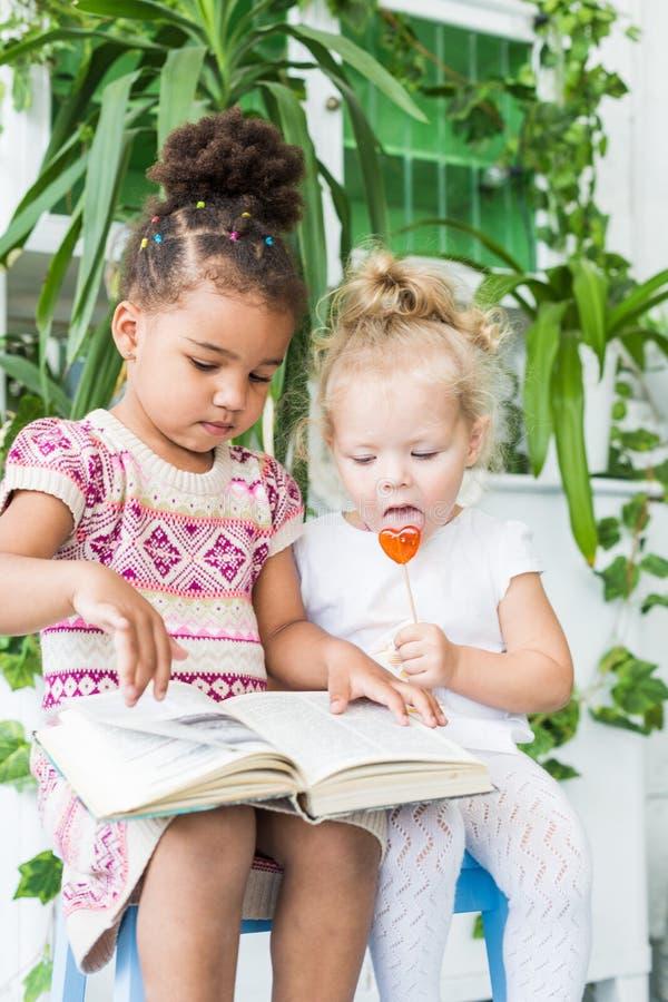 Två små flickor läste en bok på bakgrunden av växter i krukor royaltyfria foton