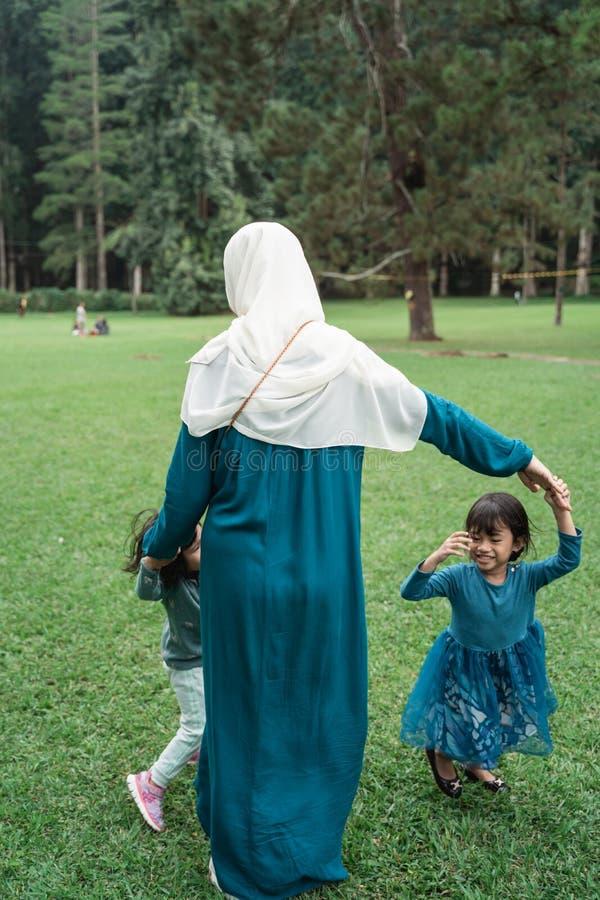 Två små flickor med deras mödrar som tillsammans spelar arkivfoton