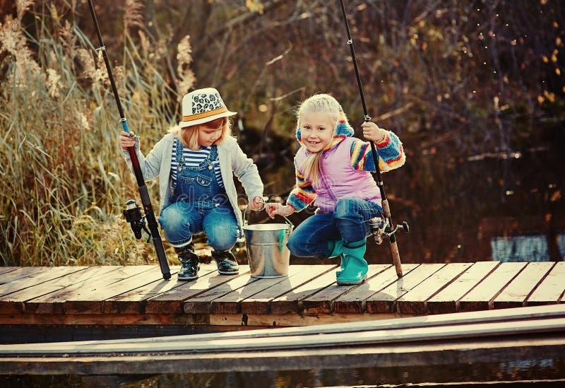 Två små flickor med metspön som sitter på en träponton och skryta av den fångade fisken arkivbild