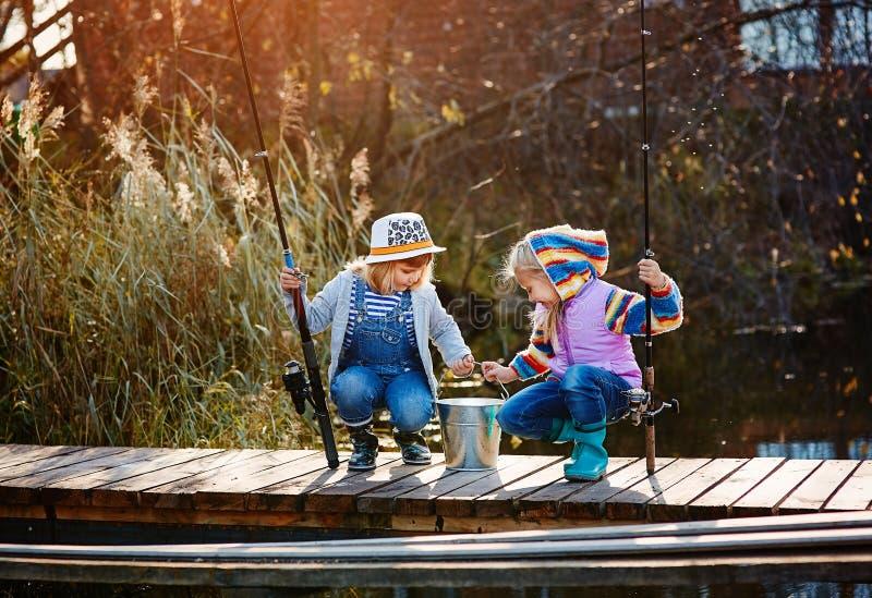 Två små flickor med metspön som sitter på en träponton och skryta av den fångade fisken royaltyfri bild