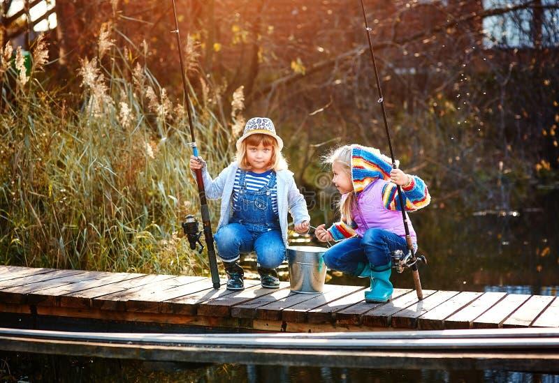 Två små flickor med metspön som sitter på en träponton och skryta av den fångade fisken royaltyfri fotografi