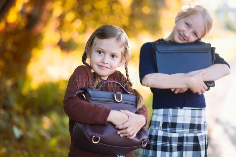 Två små flickor ordnar till tillbaka till skolacloseupen, höstdag royaltyfri bild