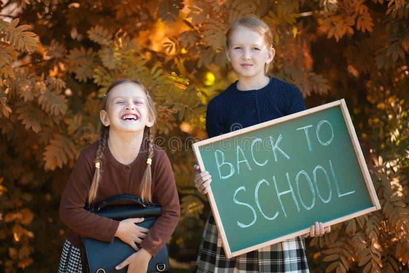 Två små flickor ordnar till tillbaka till skolan arkivfoto