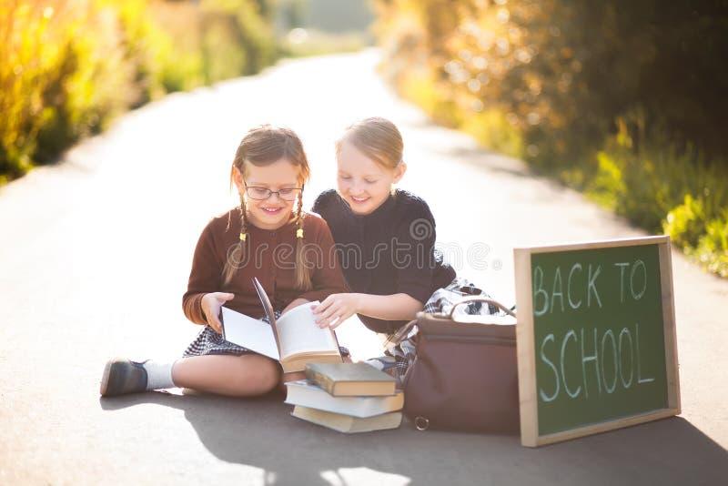 Två små flickor ordnar till tillbaka till skolan arkivbild