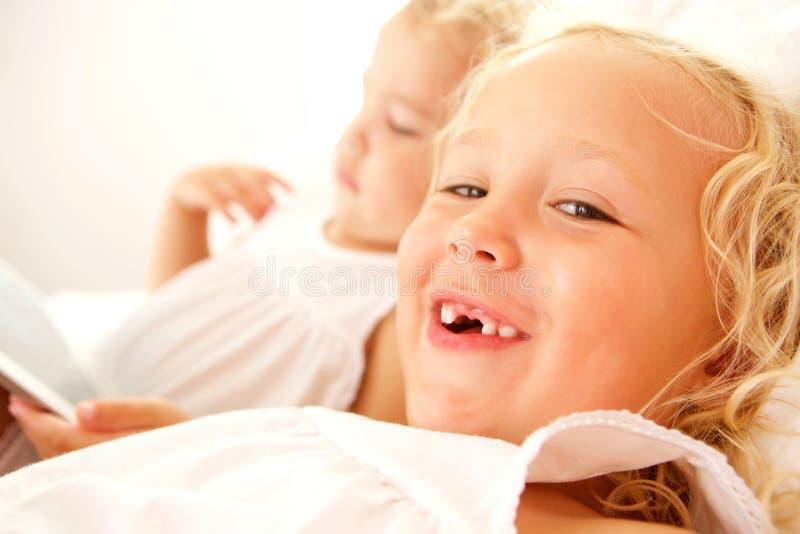 Två små flickor på säng hemma arkivfoto
