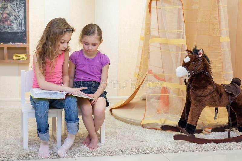 Två små flickor sitter i det modiga rummet arkivfoton
