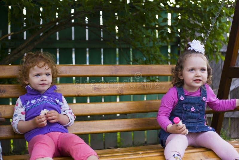 Två små flickor sitter på en hängande bänk och äter kakor royaltyfria bilder