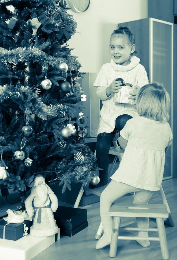 Två små flickor som dekorerar julgranen royaltyfria bilder