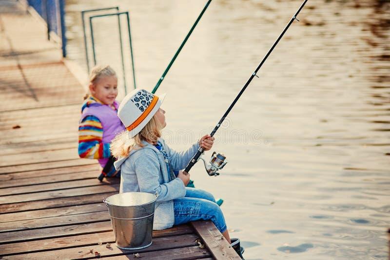 Två små flickor som fiskar på sjön på en solig morgon royaltyfria foton