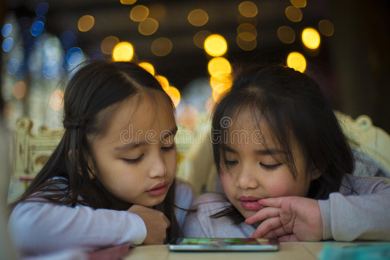 Två små flickor som håller ögonen på en video på mobiltelefonen royaltyfri foto