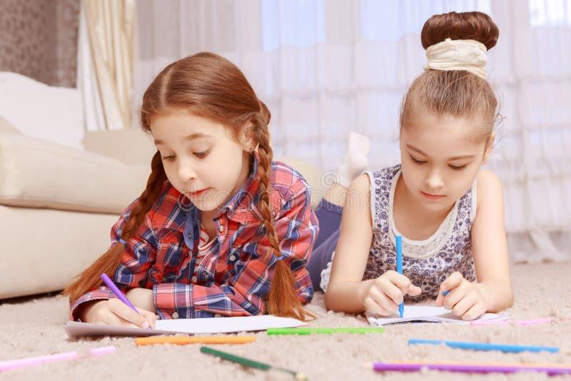Två små flickor som ligger på matta royaltyfri bild