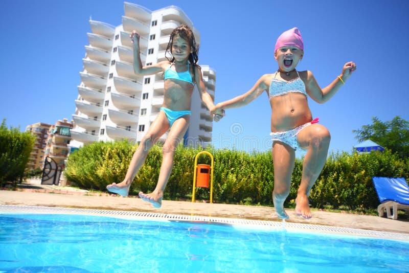 Två små flickor som rymmer rolig banhoppning för händer in i simbassängen royaltyfria bilder