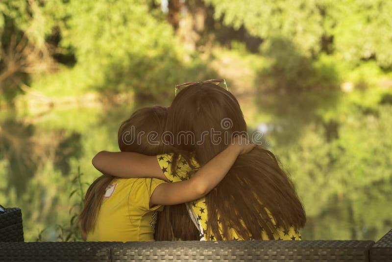 Två små flickor som sitter på gräs De två små flickorna som sitter på flodbanken, på en solig varm sommardag arkivfoton