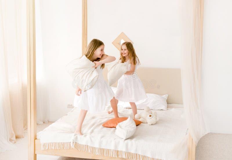 Två små flickor som slåss med kuddar på sängen royaltyfri bild