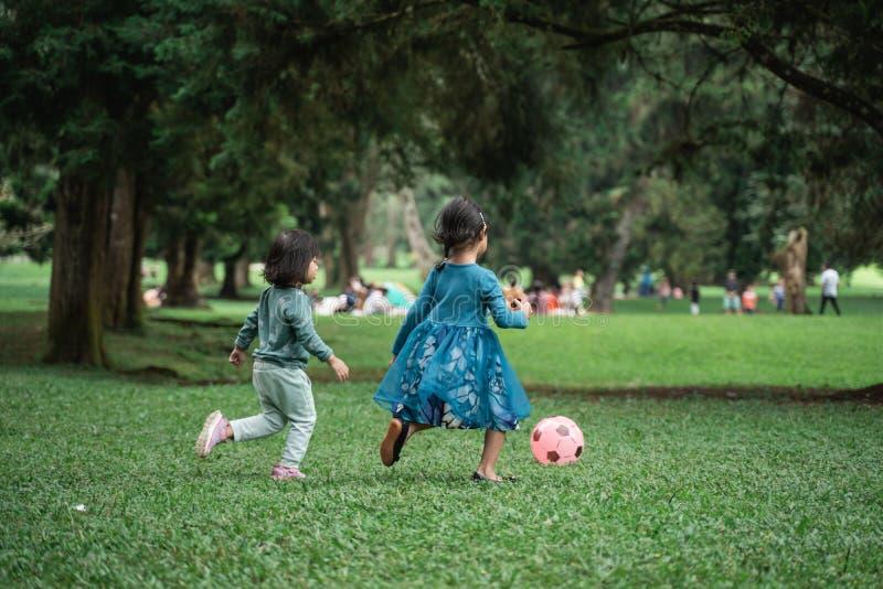Två små flickor som spelar bollen arkivbilder
