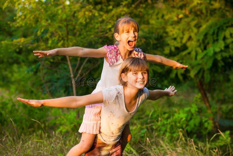 Två små flickor som spelar flugan i sommar, parkerar Begrepp av familjen royaltyfri foto