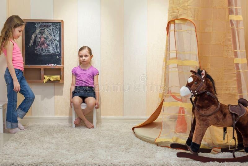 Två små flickor som spelar i gameroomen royaltyfri foto