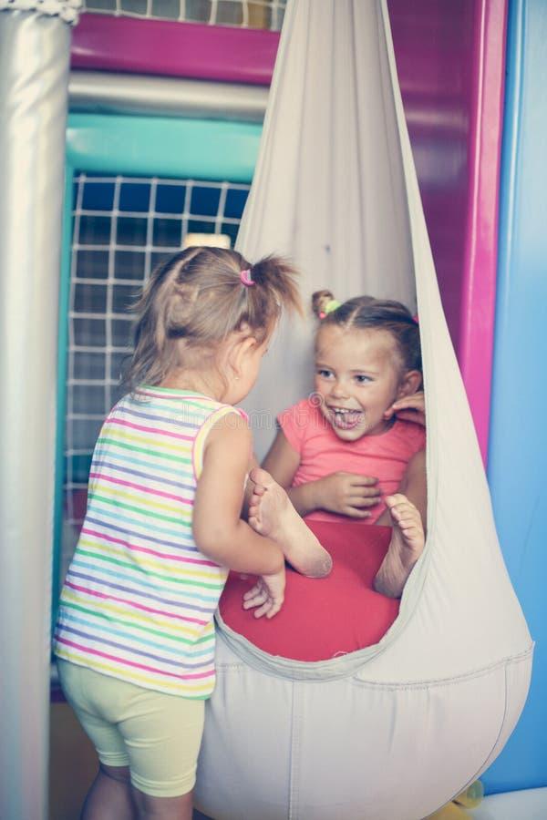 Två små flickor som spelar i lekplats royaltyfri foto