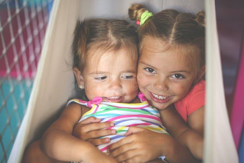Två små flickor som spelar i lekplats Små systrar som spelar t royaltyfria foton