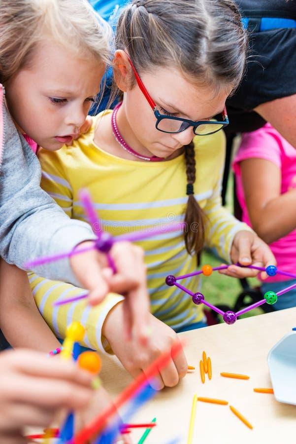 Två små flickor som spelar med massor av färgrik plast- pinneki royaltyfri fotografi