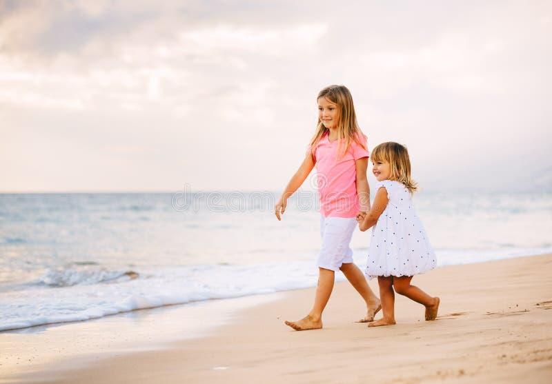 Två små flickor som tillsammans går på stranden på Sunet arkivfoto