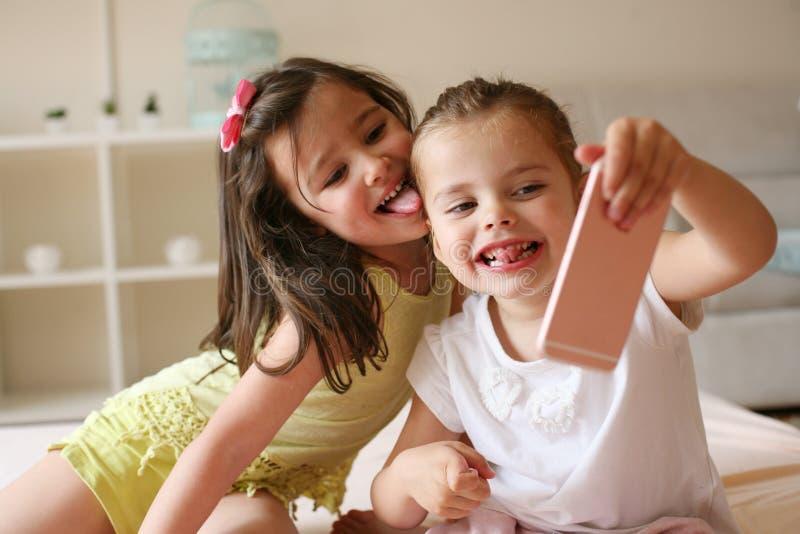 Två små flickor som tillsammans sitter på säng royaltyfri bild