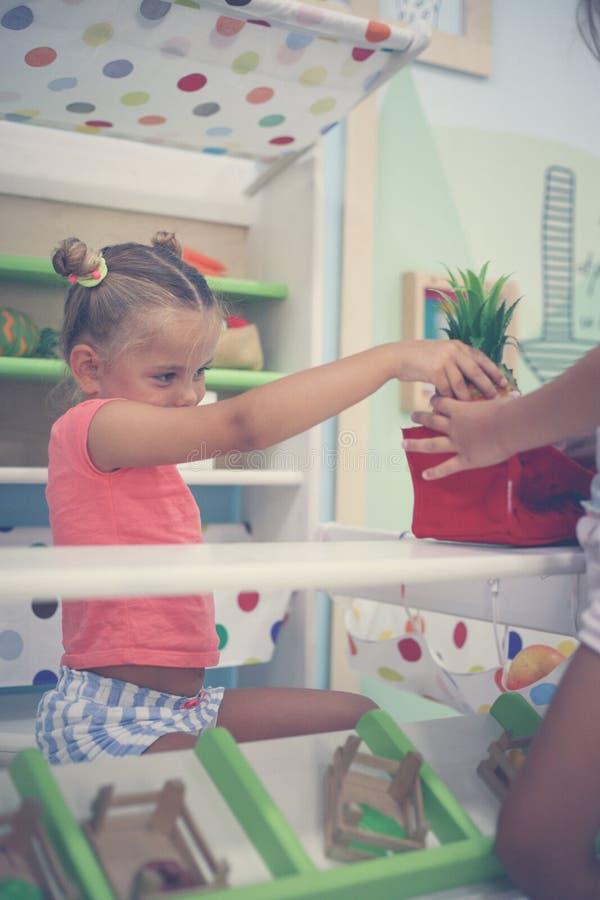 Två små flickor som tillsammans spelar i lekplats Liten flickagiv arkivbild
