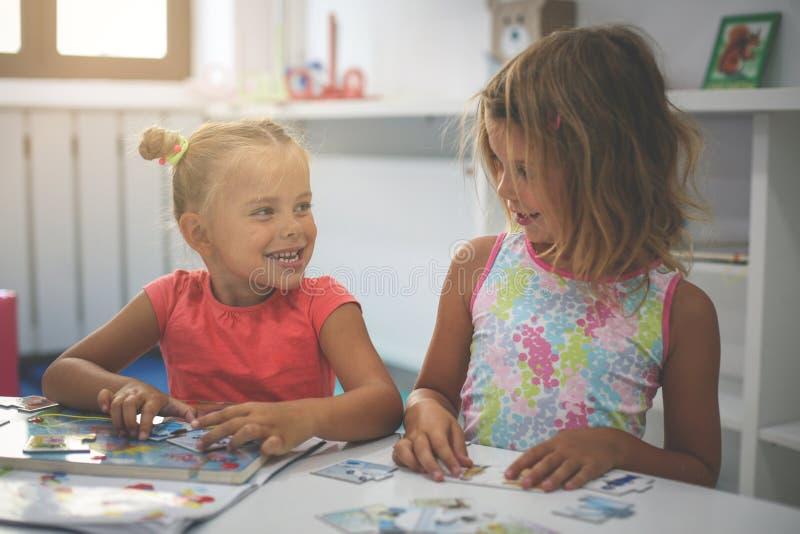 Två små flickor som tillsammans spelar i lekplats Två systrar royaltyfri fotografi