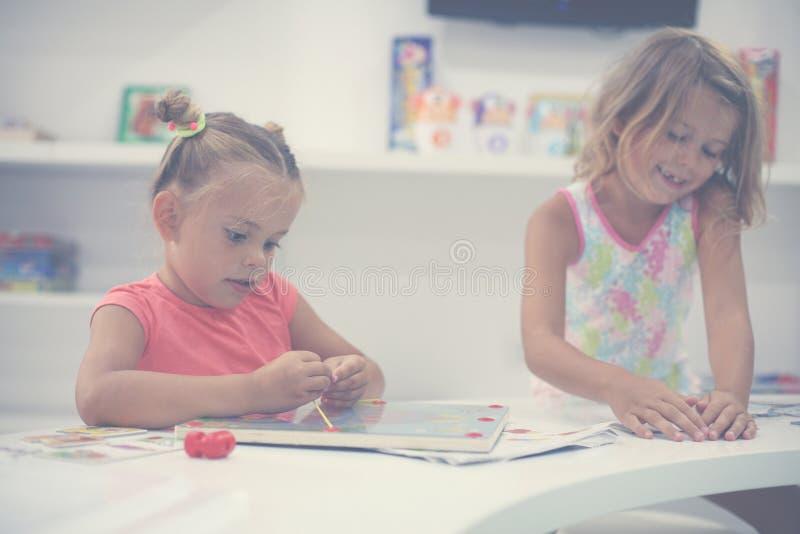 Två små flickor som tillsammans spelar i lekplats Två systrar arkivfoton