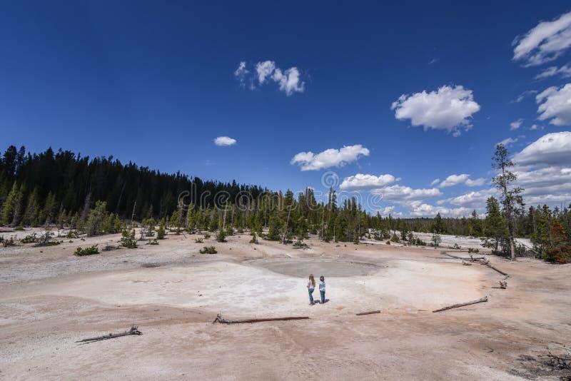 Två små flickor som undersöker gyttjan, lägger in på den klara sjön som fotvandrar slingan nära Grand Canyon av Yellowstonet Rive arkivfoton