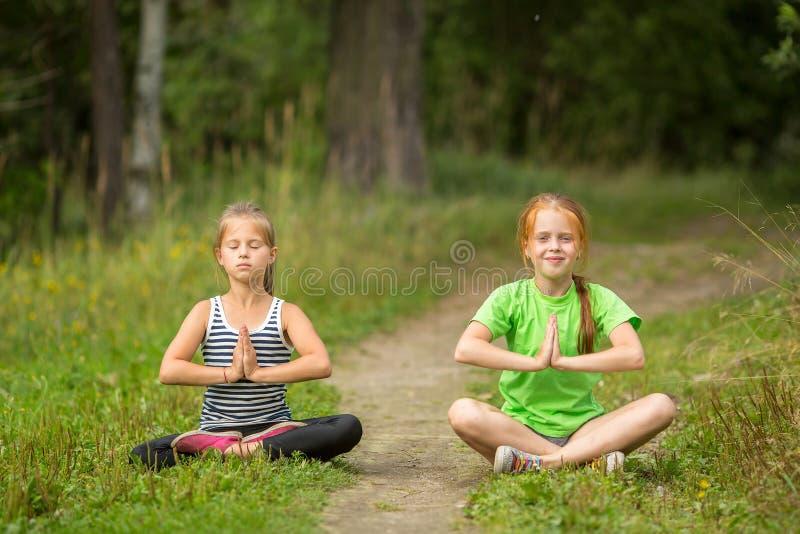 Två små flickor som utomhus sitter i yogameditation royaltyfri foto