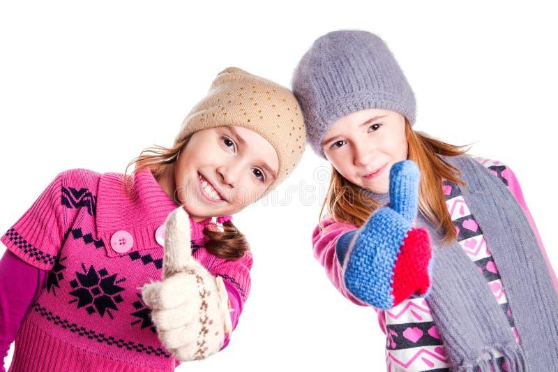 Två små flickor som visar upp tummarna royaltyfria foton