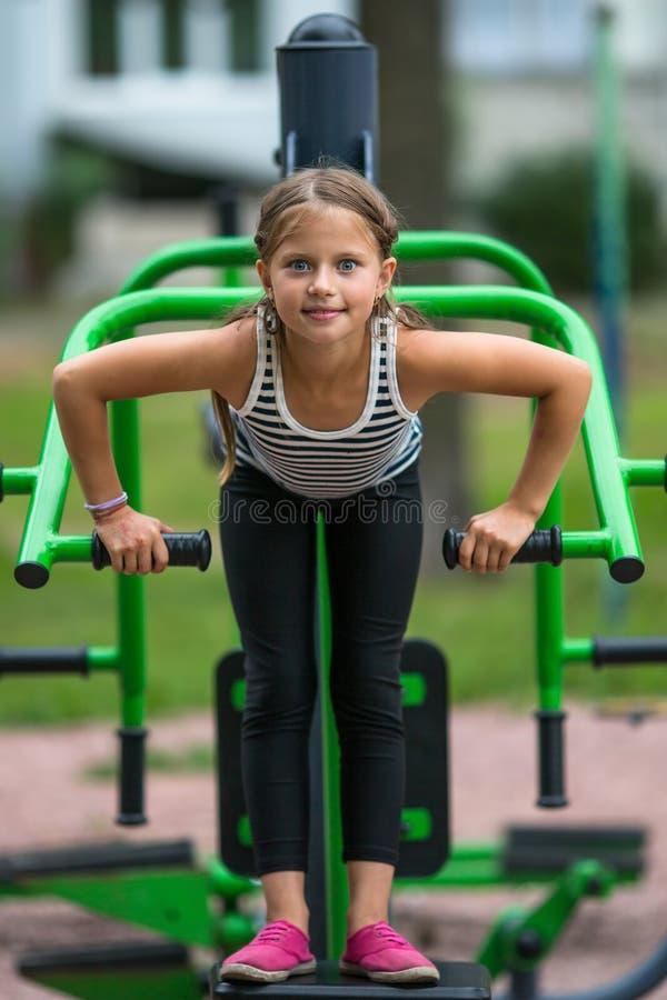 Två små flickor utför gymnastiska övningar utomhus sport arkivfoton