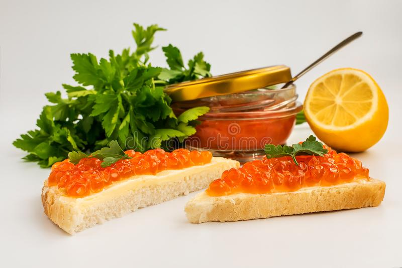 Två smörgåsar med den röda kaviaren och smör på bakgrunden av en krus av kaviaren, citron, persilja Laxkaviar Läckerhet för havsf arkivbild