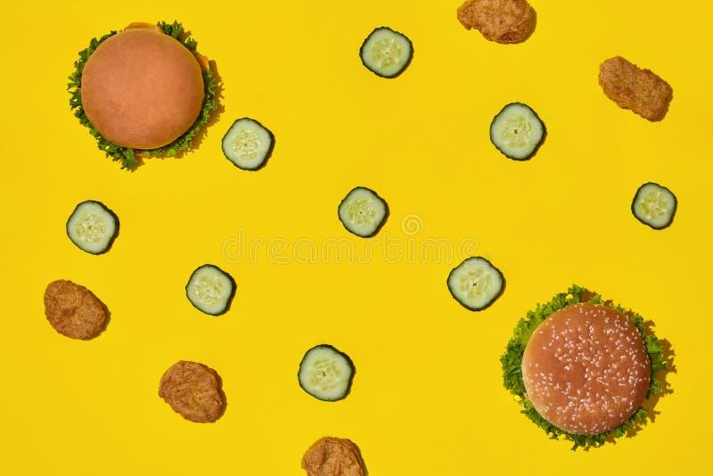 Två smakliga nya sjukliga hamburgare med ketchup och grönsaker på gul vibrerande ljus bakgrund Bästa sikt med kopian arkivbilder
