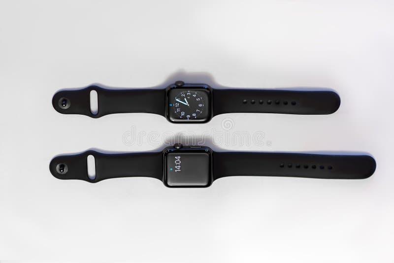 Två smarta elektroniska klockor på vit bakgrund, med jämbördig tid på skärmarna royaltyfri fotografi