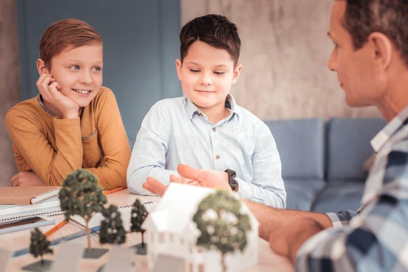 Två smarta nyfikna pojkar som uppmärksamt lyssnar till deras farbror arkivbild