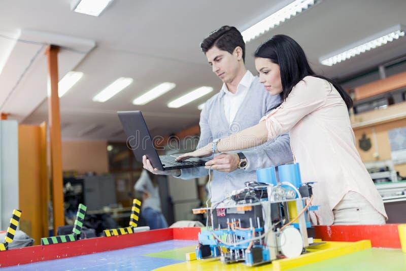Två smarta studenter som programmerar en robot arkivbild
