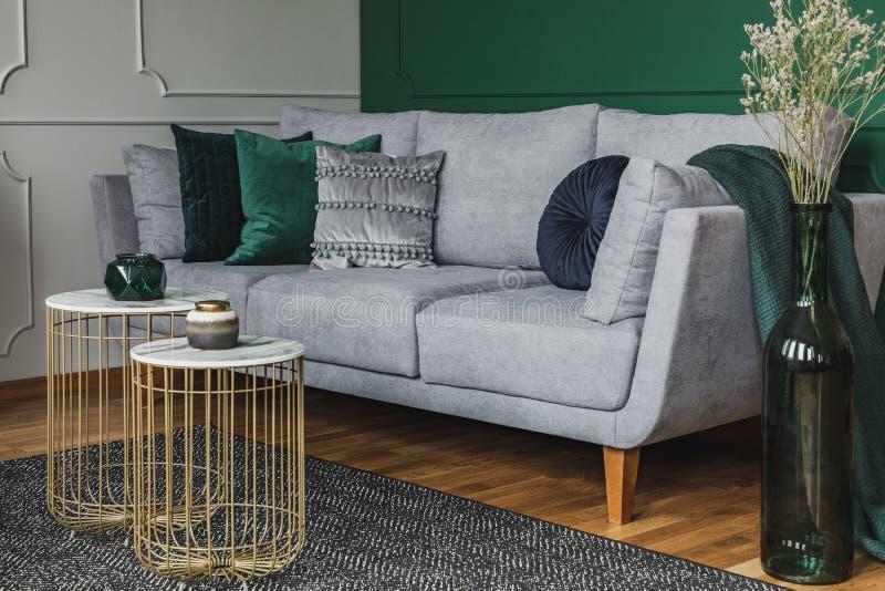 Två snygga små kaffebord med marmortoppar framför elegant grå soffa med smarta kuddar royaltyfri fotografi