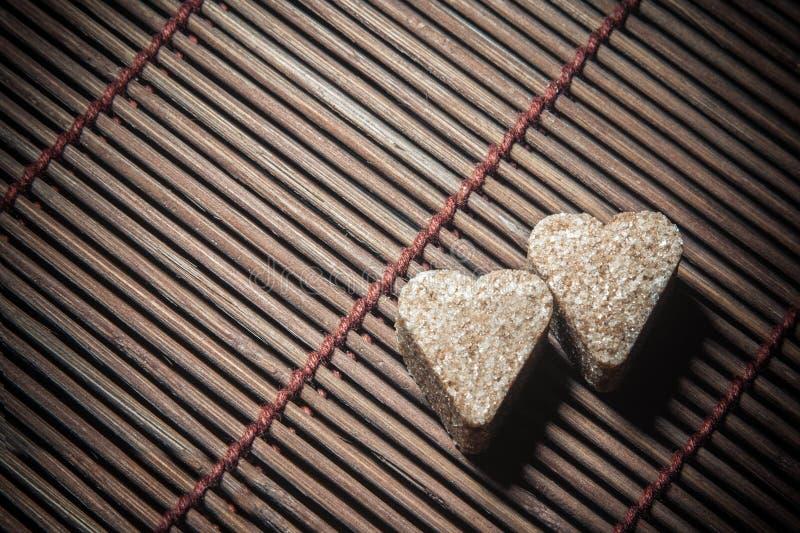 Två sockerhjärtor på trätextur royaltyfri foto