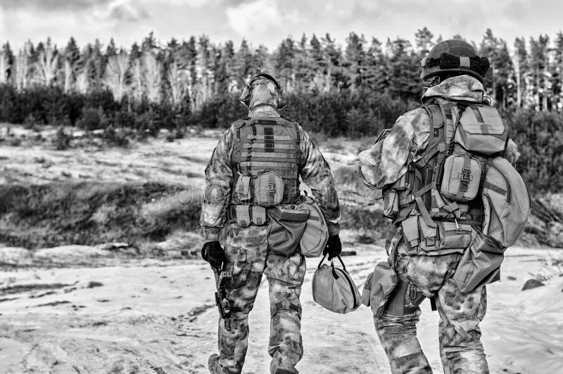 Två soldater av en special enhet förbereder sig att bära ut en farlig beskickning royaltyfri fotografi