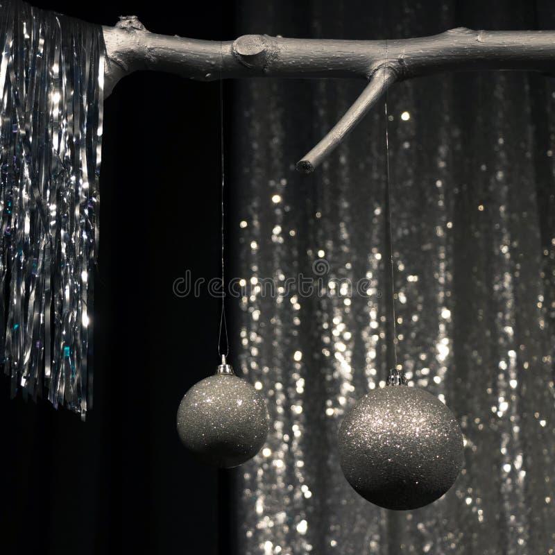 Två som hänger, försilvrar julbollar på mörkt och försilvrar bakgrund arkivfoton