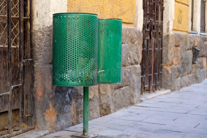 Två sopburkar på stadsgatan mot väggen arkivbild